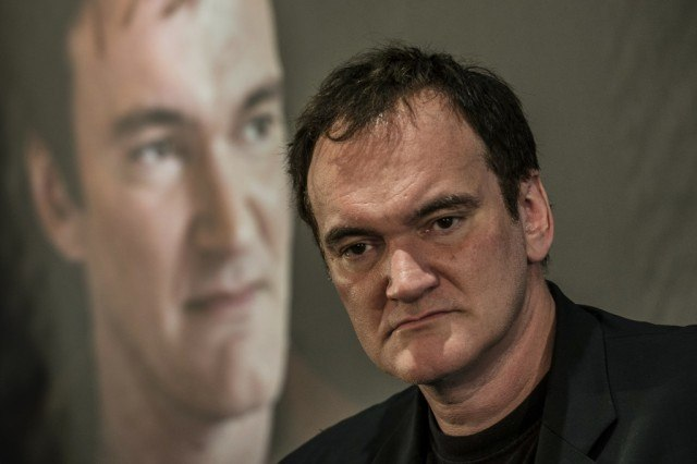 Quentin Tarantino in front of a photo of himself.