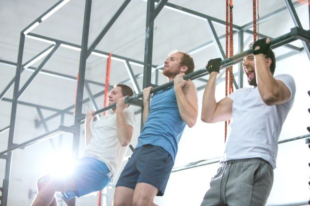 three men on pull-up bar in gym