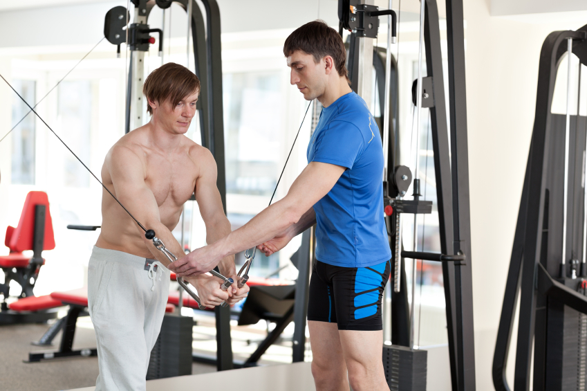 A personal trainer instructs a man at the gym