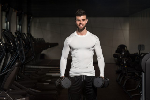 muscular man holding dumbbells to get ready to lift