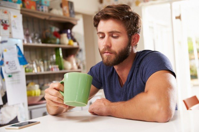 A man stares into a mug while sitting at a table.
