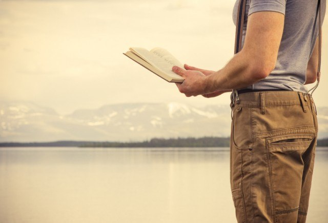 Man reading a book by the lake