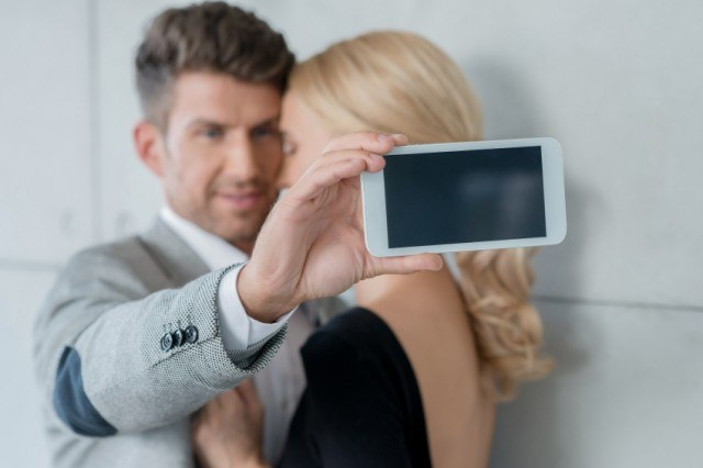 Man and woman taking a picture together on a smartphone