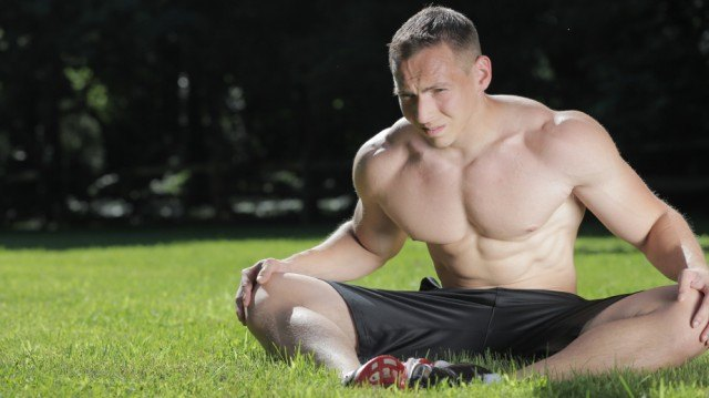 man sitting in the grass to stretch