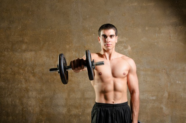man holding a weight in front of him