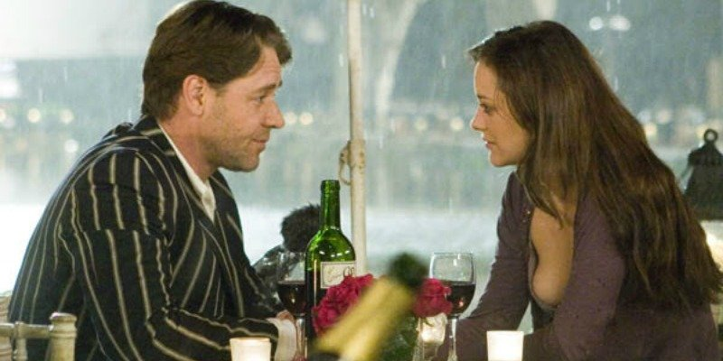 Russell Crowe and Marion Cotillard look at each other over a bottle of wine and glasses