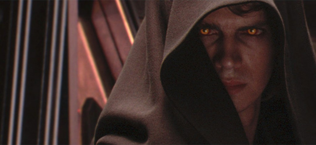 Anakin Skywalker, with yellow eyes and a brown hood, looking angrily off into the distance