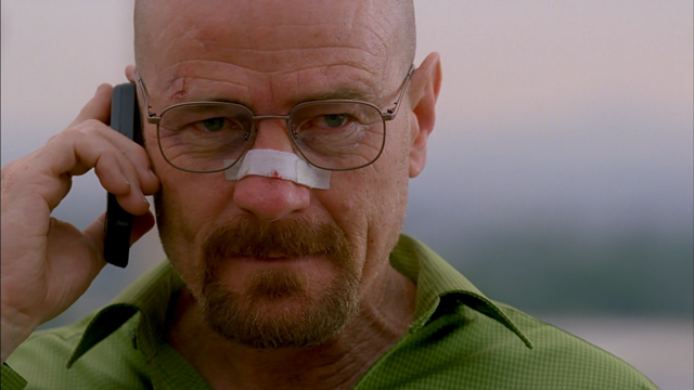 Bryan Cranston as Walter White holding a cell phone to his ear with a bandage on his nose on Breaking Bad
