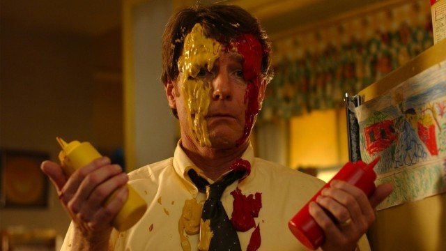 Hal holds a bottle of mustard and ketchup while smeared in both.