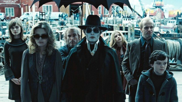 Johnny Depp and others in Dark Shadows standing under a black umbrella in a shipyard