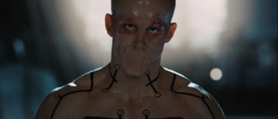 Deadpool, with his mouth sewn shut, shirtless and staring into the camera angrily