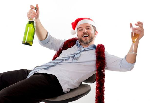 Drunk businessman drinking champagne wearing Santa hat