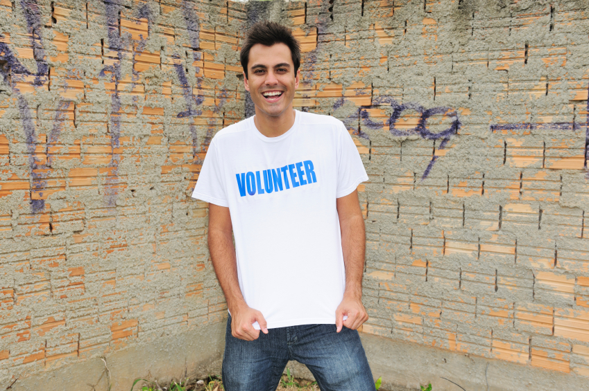 "A happy young man wearing jeans and a shirt that says ""Volunteer"""