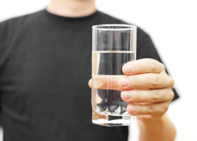 man hydrating with glass of water