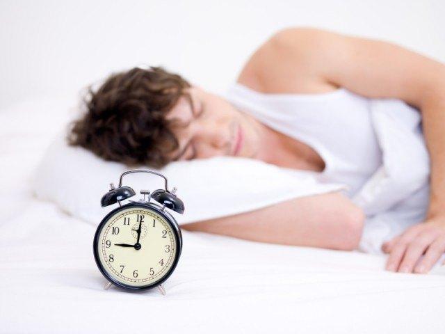 man sleeping next to a ticking alarm clock