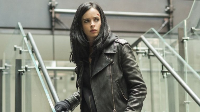 Krysten Ritter in a black leather jacket holds onto a glass railing