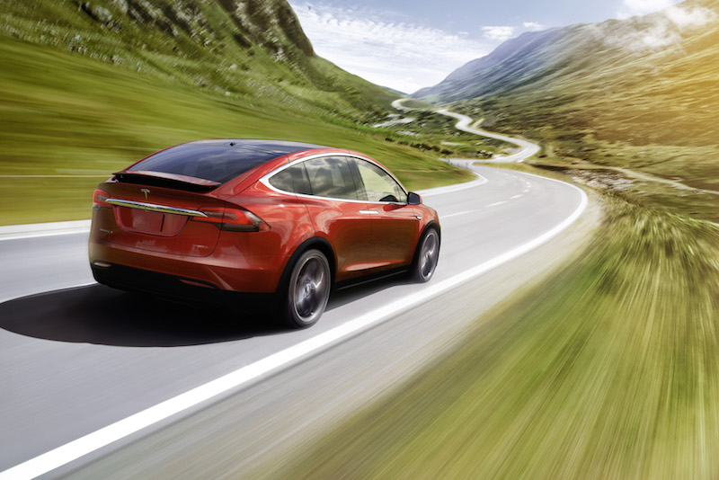 A red Tesla Model X speeding down a scenic road