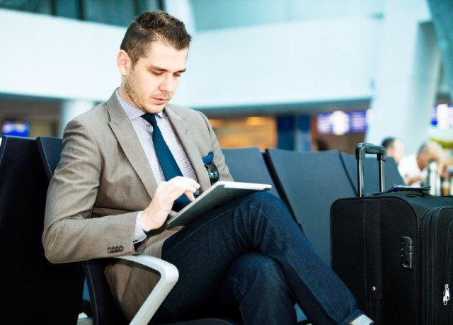 Traveler reading on a tablet in the airport