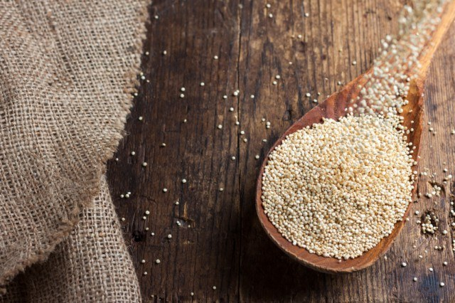 Quinoa on a wooden table and spoon.