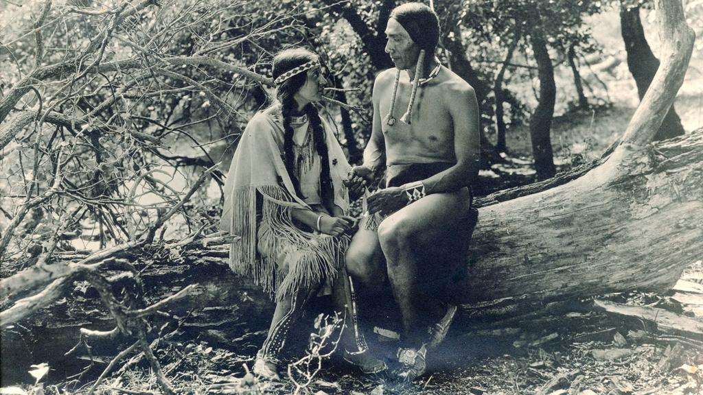 A Native American woman and man sitting on a fallen tree in the forest in a scene from The Daughter of Dawn