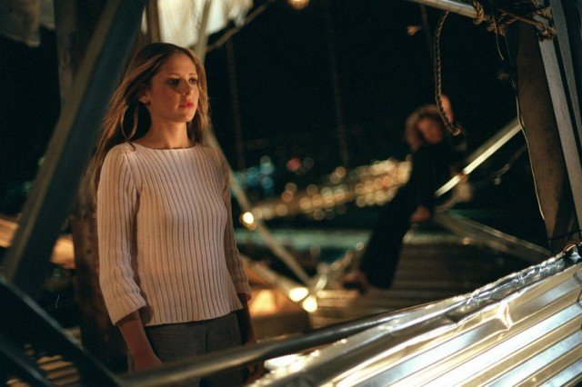 Sarah Michelle Gellar as Buffy Summers on Buffy the Vampire Slayer in a white sweater on a steel structure