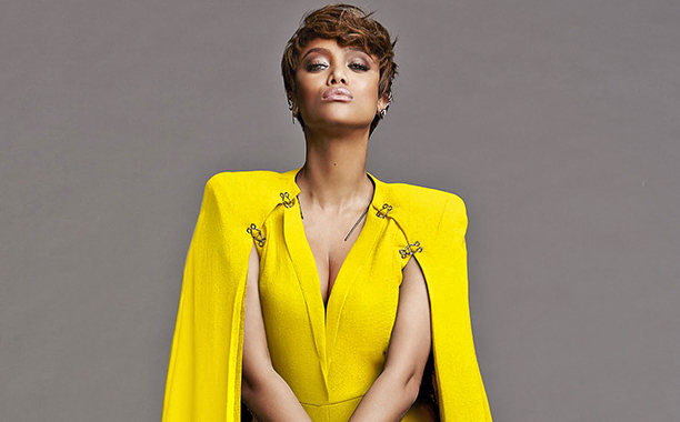 Tyra Banks in a yellow gown in front of a gray wall.
