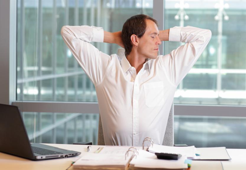 Man stretching at work desk