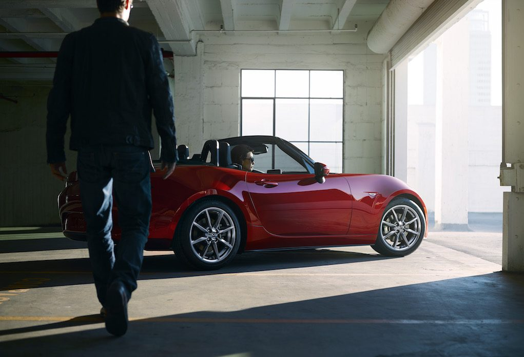Drivers side profile view of red Mazda MX-5 Miata in garage