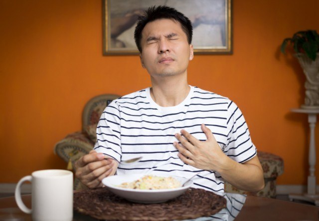 Man has heartburn while eating his meal
