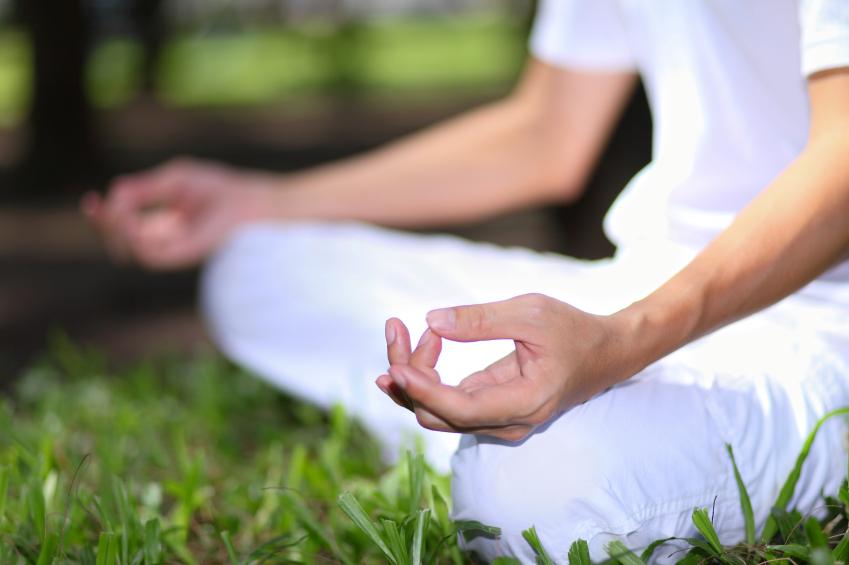 A man meditating outside to increase positive energy