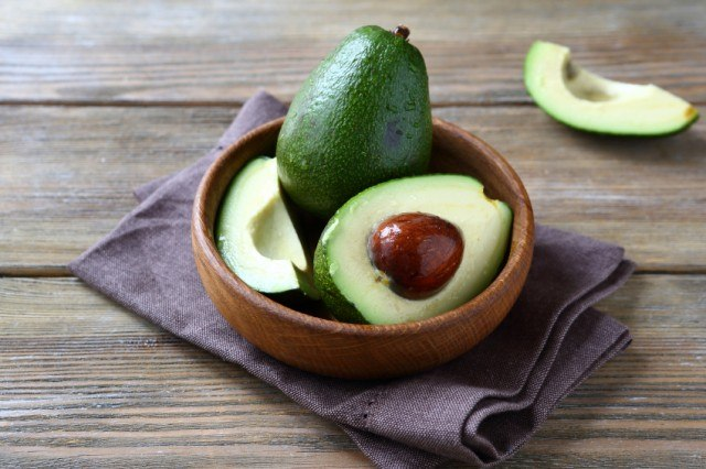 whole and halved avocado in a wooden bowl