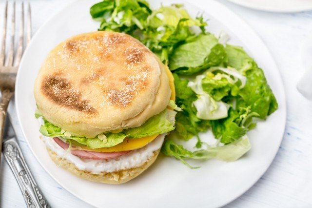 breakfast sandwich with cheese, eggs, ham, and lettuce on an English muffin with a side salad