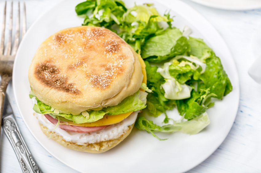 breakfast sandwich with cheese, eggs, ham, and lettuce on an English uffin with a side salad