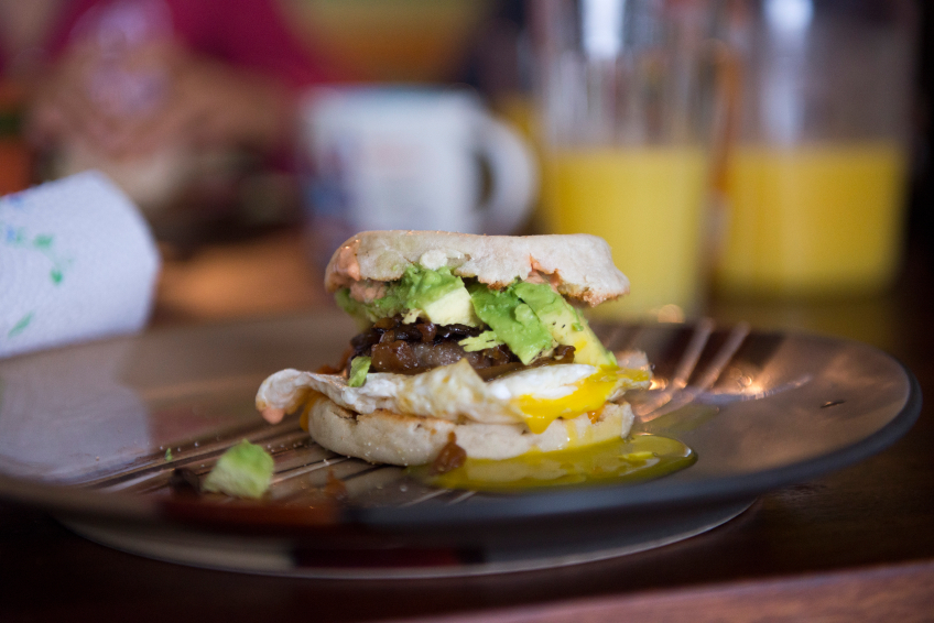 breakfast sandwich with egg, sausage, and avocado, english muffin