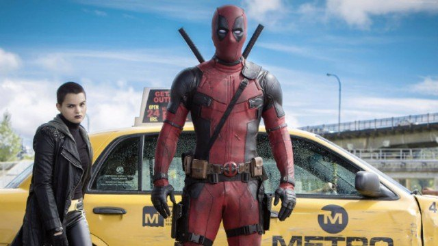 Ryan Reynolds as 'Deadpool' in front of a car.