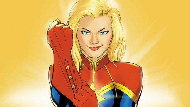 Captain Marvel, putting on a glove and smiling into the camera