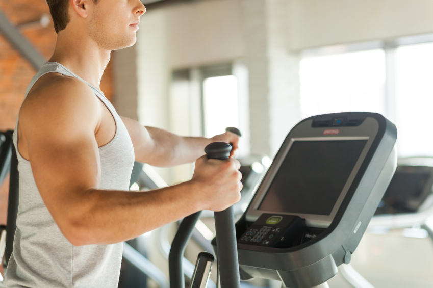 man working out on an elliptical trainer at the gym