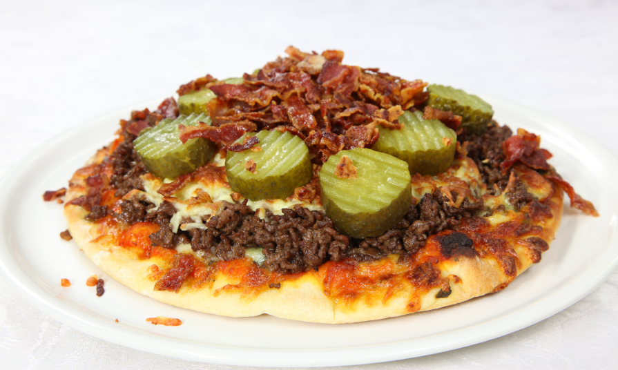 bacon cheeseburger pizza with pickles on a white plate