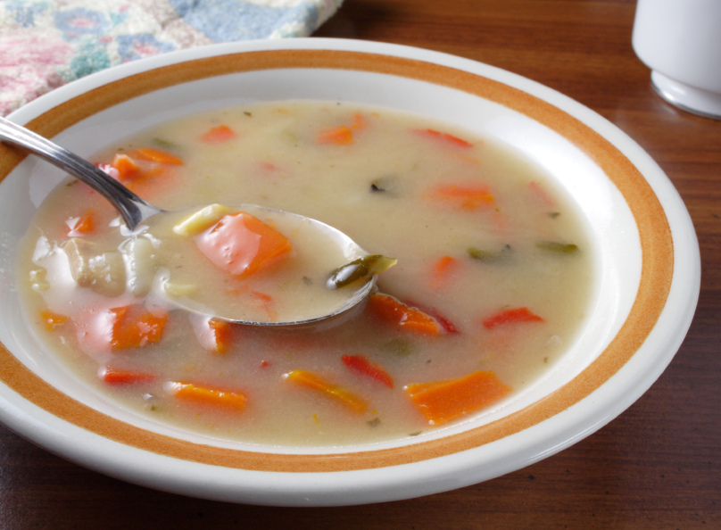 creamy soup with vegetables and chicken in a white bowl on a wooden table