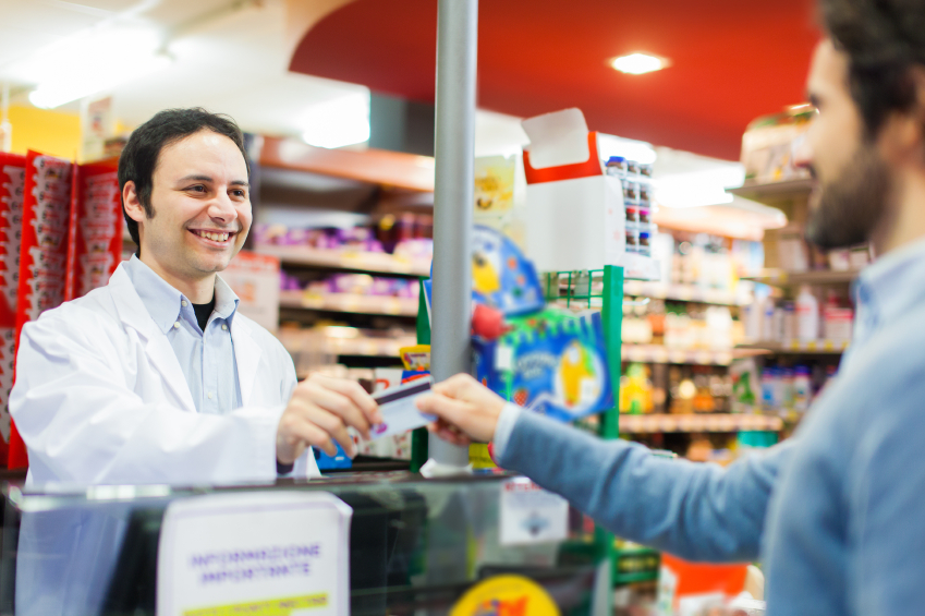 man talking to a cashier and handing him his credit card