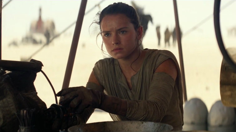 Rey repairs a broken part, while staring off into the distance