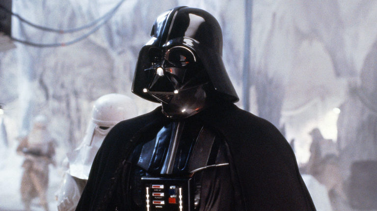 Darth Vader stands in an icy cave, looking off to the left of the screen