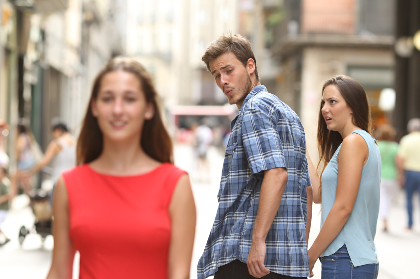 man checking out another woman in front of his partner