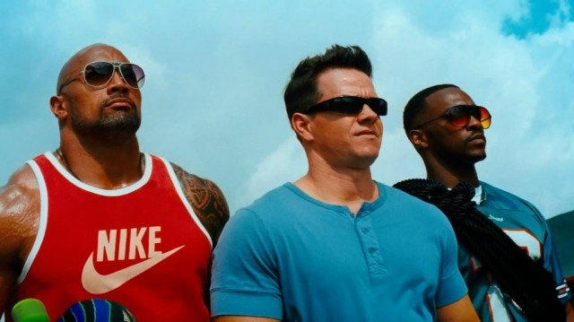 Dwayne Johnson, Mark Wahlberg and Anthony Mackie stand next to each other outdoors in 'Pain & Gain'
