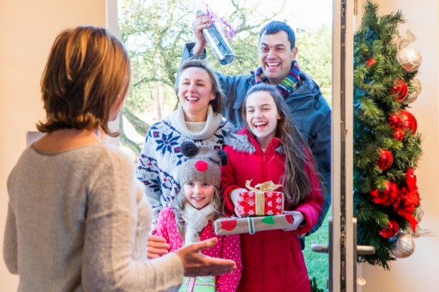 woman opening door to family during holidays