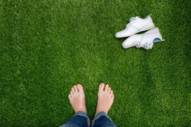 A person enjoys the feel of green grass beneath their feet