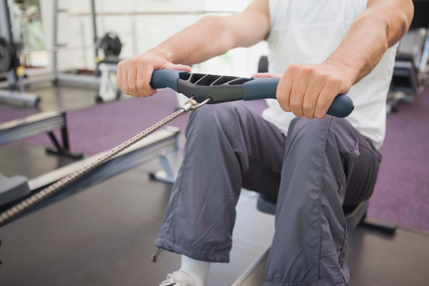 close-up of man working out on a rowing machine at the gym