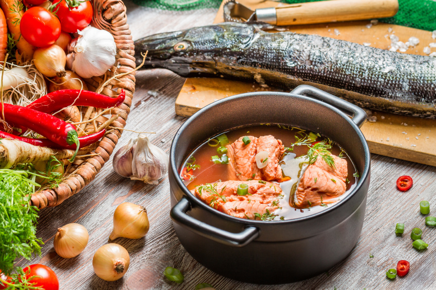 making spicy fish soup with chiles and fresh fish in a heavy pot