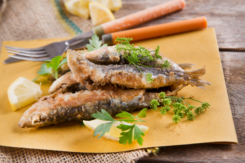 fried sardines with lemon and parsley on parchment paper