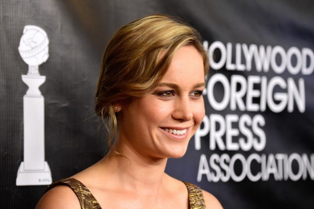 Brie Larson smiling while wearing a gold dress.
